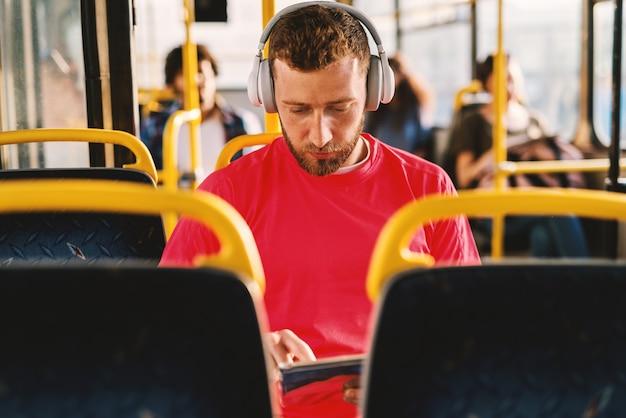 Joven escuchando música, sentado en un autobús, buscando en la web.
