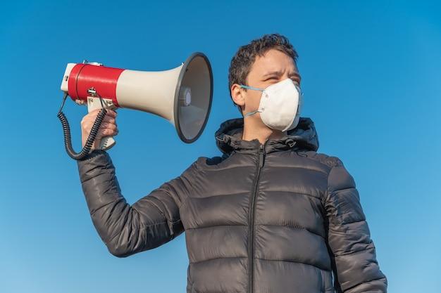 El joven está escuchando nueva información y noticias del megáfono sobre la epidemia de coronavirus en el mundo.