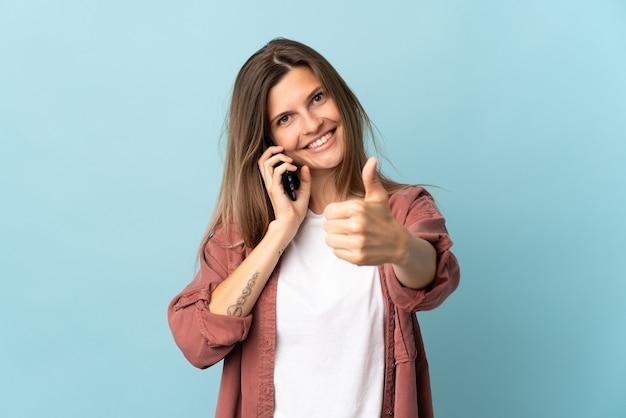 Joven eslovaca aislada en la pared azul manteniendo una conversación con el móvil mientras hace los pulgares hacia arriba