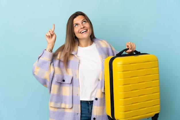 Joven eslovaca aislada en la pared azul en vacaciones con maleta de viaje y apuntando hacia arriba