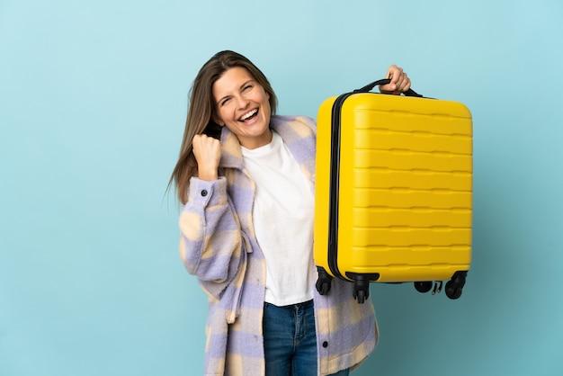 Joven eslovaca aislada en la pared azul en vacaciones con maleta de viaje