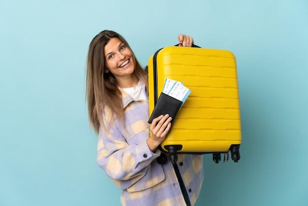 Joven eslovaca aislada sobre fondo azul en vacaciones con maleta y pasaporte