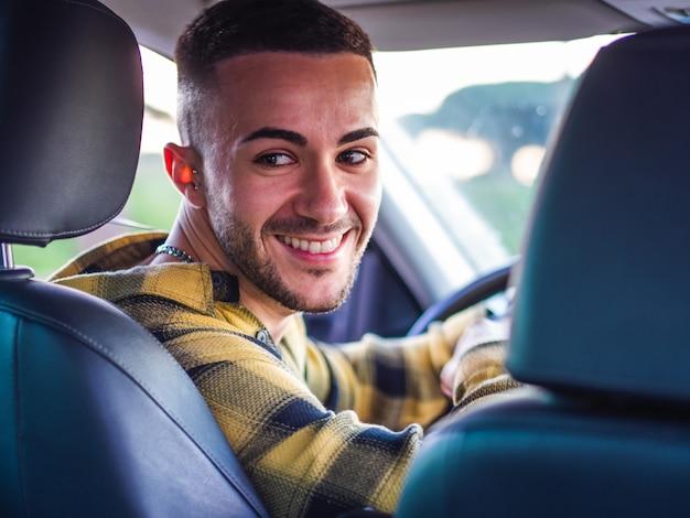 Joven español sonriendo y conduciendo un coche