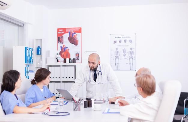 Joven especialista médico discutiendo sobre el diagnóstico del paciente con compañeros de trabajo en la sala de conferencias del hospital. terapeuta experto de la clínica hablando con colegas sobre la enfermedad, profesional de la medicina