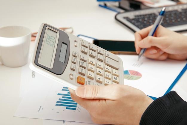 Un joven especialista trabaja con documentos financieros en una computadora.