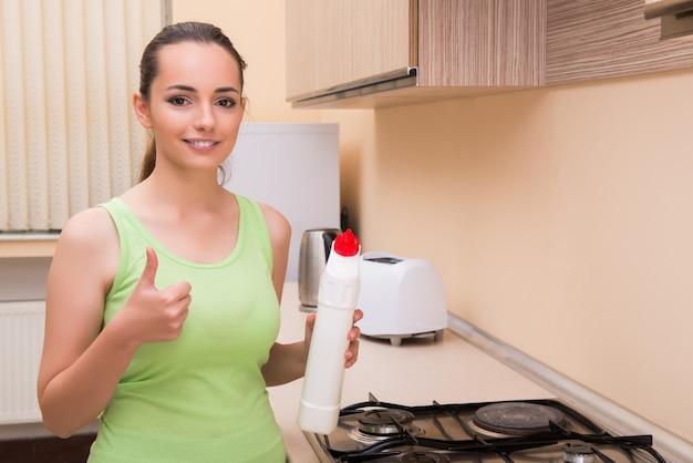 Joven esposa limpieza cocina sosteniendo la botella