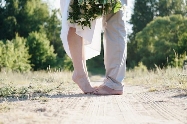 Joven esposo y esposa descalzo en un camino rural con un hermoso ramo de flores