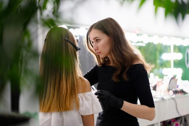 Joven esteticista niña caucásica tiene corrección de cejas modelo
