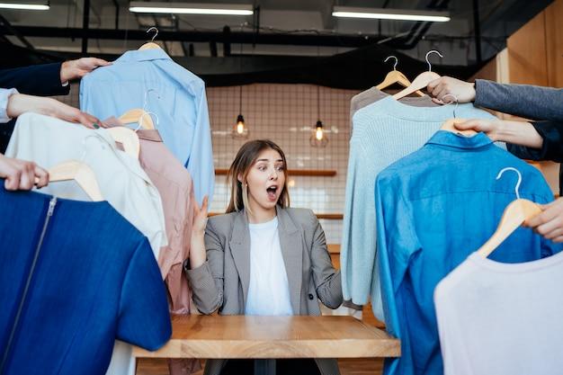Joven estilista mirando a través de un conjunto de camisas para disparar a la moda