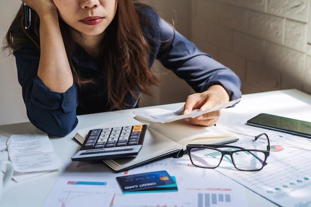 Joven estresada revisando facturas, impuestos, saldo de cuenta bancaria y calculando gastos en la sala de estar en casa
