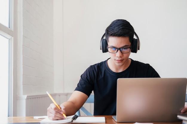 Joven estudia en casa usando una computadora portátil y aprende en línea