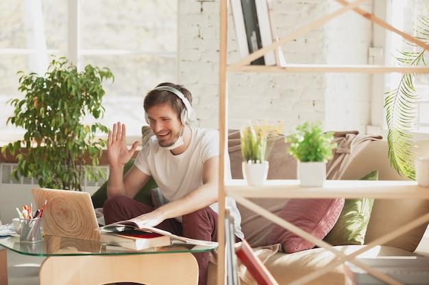 Joven estudiando en casa durante cursos en línea para traductor arquitecto comercializador