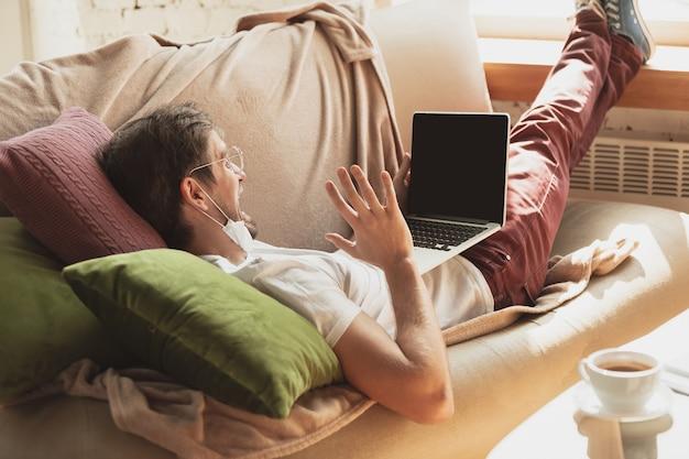 Joven estudiando en casa durante cursos online para periodistas, críticos, escritores. obtener profesión mientras está aislado, cuarentena contra la propagación del coronavirus. usando computadora portátil, teléfono inteligente, auriculares.