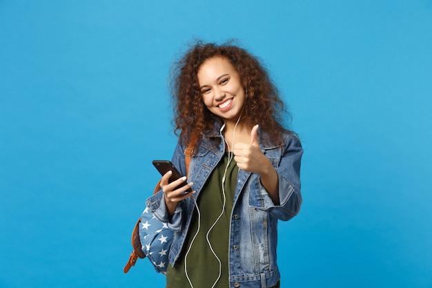 Joven estudiante adolescente afroamericana en ropa de mezclilla, auriculares de mochila aislado en la pared azul