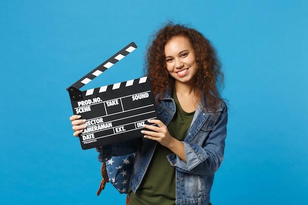 Joven estudiante adolescente afroamericana en ropa de mezclilla, badajo de sujeción de mochila aislado en la pared azul