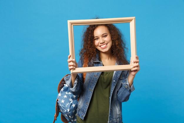 Joven estudiante adolescente afroamericana en ropa de mezclilla, marco de retención de mochila aislado en la pared azul