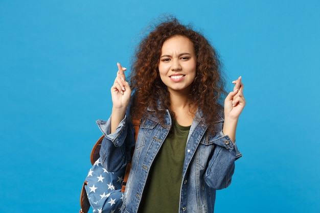 Joven estudiante adolescente afroamericana en ropa de mezclilla, mochila haciendo deseo aislado en la pared azul