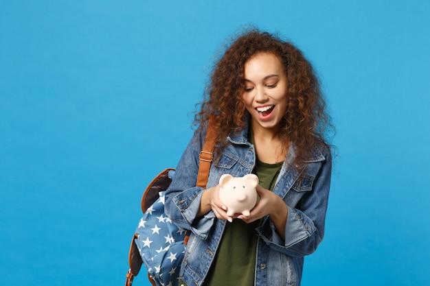 Joven estudiante adolescente afroamericana en ropa de mezclilla, mochila mantenga cerdo aislado en la pared azul