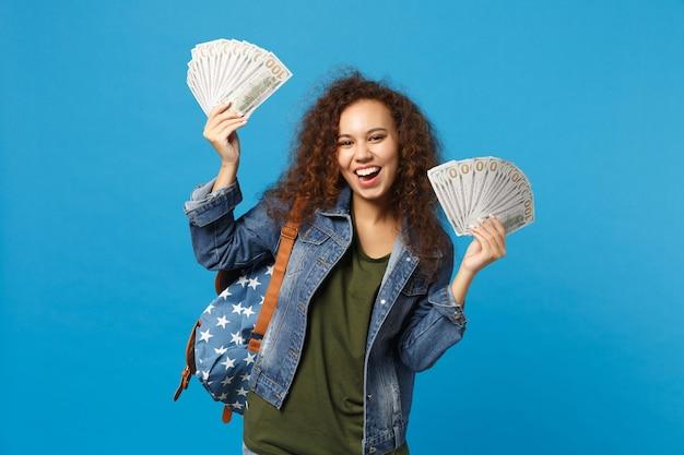 Joven estudiante adolescente afroamericana en ropa de mezclilla, mochila mantenga dinero en efectivo aislado en la pared azul