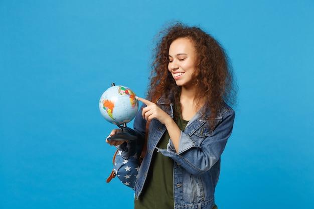 Joven estudiante adolescente afroamericana en ropa de mezclilla, mochila mantenga globo aislado en la pared azul