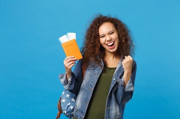 Joven estudiante adolescente afroamericana en ropa de mezclilla, mochila mantenga pase aislado en la pared azul