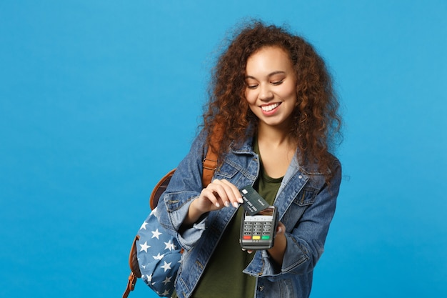 Joven estudiante adolescente afroamericana en ropa de mezclilla, mochila mantenga tarjeta de crédito aislada en la pared azul
