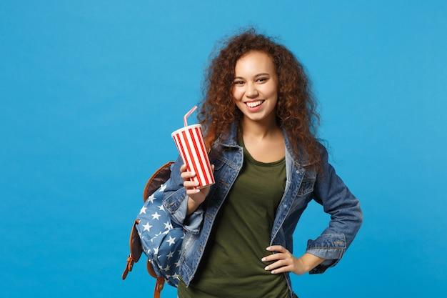 Joven estudiante adolescente afroamericana en ropa de mezclilla, mochila mantenga taza de papel aislada en la pared azul