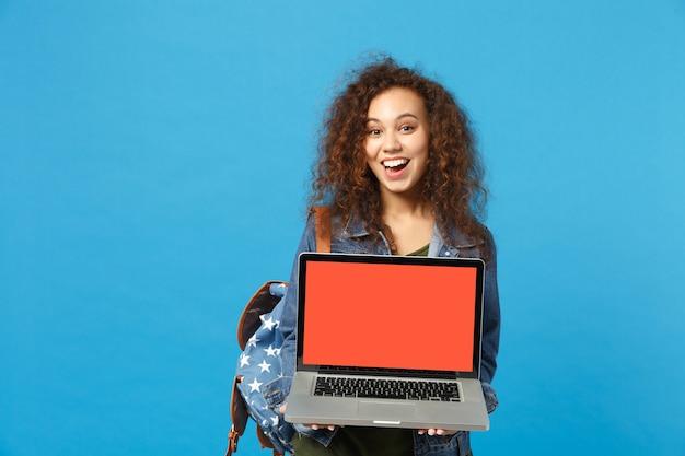 Joven estudiante adolescente afroamericana en ropa de mezclilla, mochila de trabajo en pc aislado en la pared azul