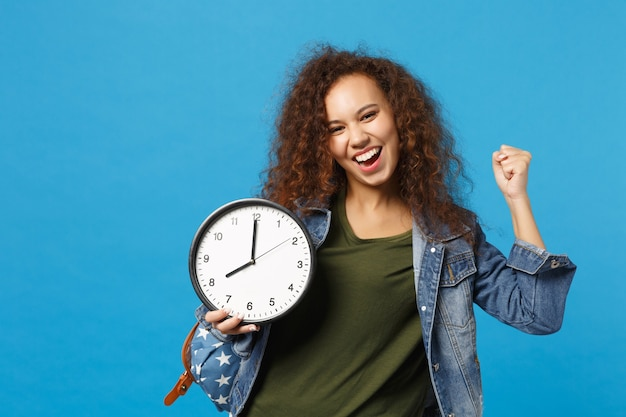 Joven estudiante adolescente afroamericana en ropa de mezclilla, reloj de retención de mochila aislado en la pared azul