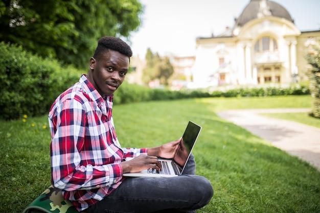 Joven estudiante africano sonriente sentado en la hierba con el portátil al aire libre en verano