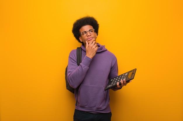 Joven estudiante afroamericano hombre sosteniendo una calculadora dudando y confundido