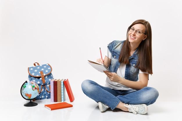 Joven estudiante agradable casual en gafas escribiendo notas en el cuaderno sentado cerca del globo, mochila, libros escolares aislados