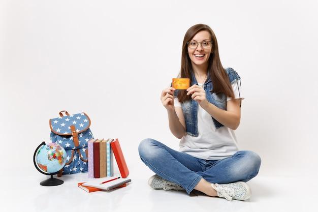 Joven estudiante alegre sorprendida en gafas ropa de mezclilla con tarjeta de crédito sentado cerca de la mochila del globo, libros escolares aislados
