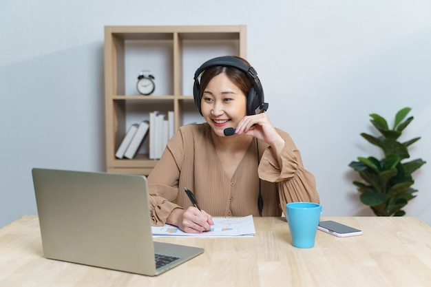 Joven estudiante asiática adulta con auriculares escucha en la pantalla del portátil aprendiendo cursos en línea