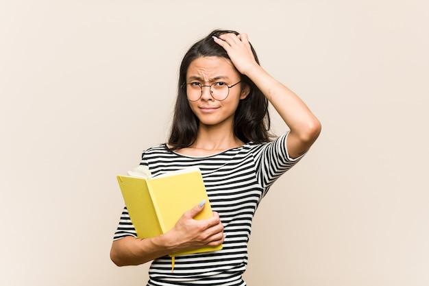 Joven estudiante asiática con un libro sorprendido, ha recordado una reunión importante.