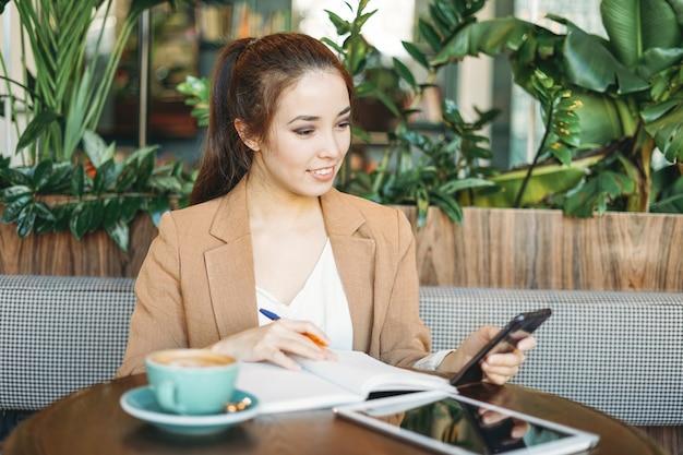 Joven estudiante asiática sonriente haciendo los deberes en el cuaderno con la tableta en la mesa usando el teléfono móvil en el café