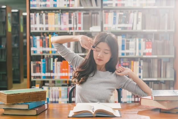 Joven estudiante asiática en traje casual leyendo y haciendo estiramiento en la biblioteca de la universidad