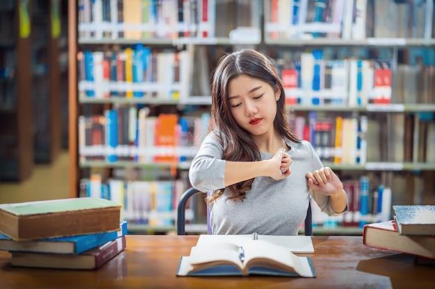 Joven estudiante asiática en traje casual leyendo y haciendo estiramientos en la biblioteca de la universidad o colegio con varios libros y papelería en la mesa de madera sobre el estante de libros, regreso a la escuela
