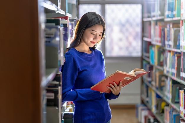 Joven estudiante asiática en traje casual de pie y leyendo el libro en el estante de libros en la biblioteca de la universidad o colegio con varias paredes de libros, concepto de regreso a la escuela