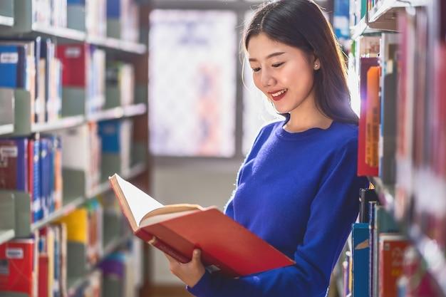 Joven estudiante asiática en traje casual de pie y leyendo el libro en el estante de libros en la biblioteca de la universidad o colegio con varios libros, regreso a la escuela