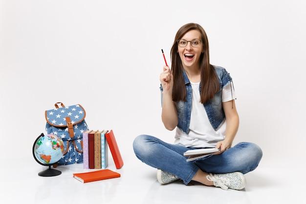 Joven estudiante asombrada iluminada con un nuevo pensamiento apuntando lápiz hacia arriba sosteniendo el cuaderno cerca de la mochila del globo, libros escolares aislados