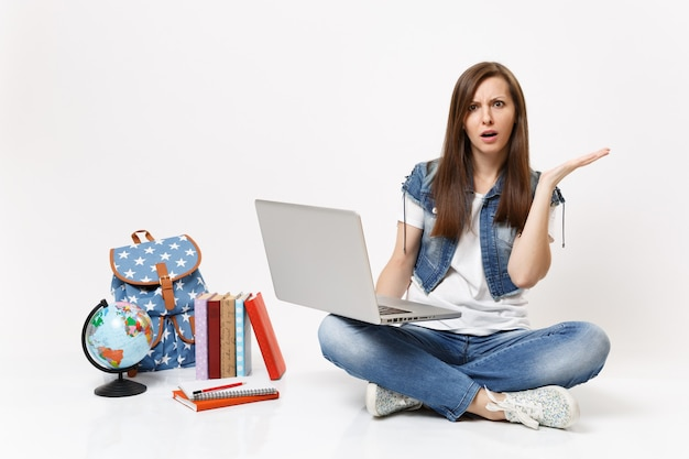 Joven estudiante asombrada mantenga usando la computadora de la pc portátil extendiendo la mano sentada cerca de la mochila del globo, libros escolares aislados