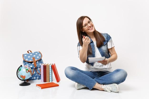 Joven estudiante atractiva en gafas apuntando con lápiz en la parte delantera, sosteniendo el cuaderno sentado cerca de los libros escolares de la mochila del globo aislado