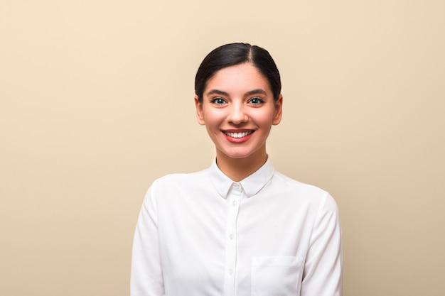 Joven estudiante atractiva mujer en camisa blanca con cuello, pelos atados y labios rojos alegre sonriendo. matrícula universitaria exitosa