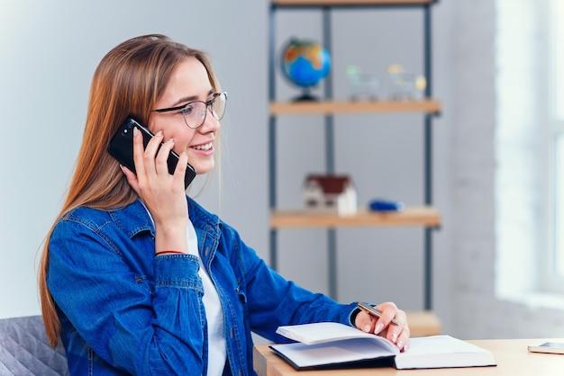 Joven estudiante atractiva utiliza teléfono inteligente mientras estudiaba en casa.