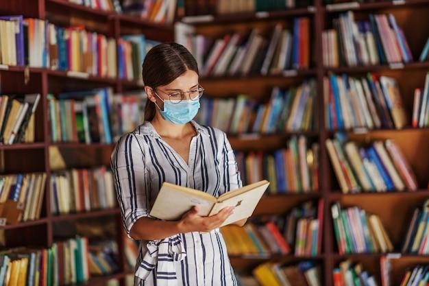 Joven estudiante atractiva en vestido con cabello castaño de pie en la biblioteca con máscara en la cara y leyendo un libro. estudiar durante la pandemia del virus corona.