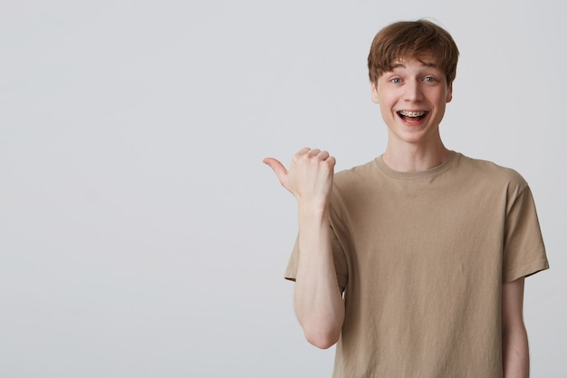 Joven estudiante atractivo indica espacio de copia con el pulgar, sonríe ampliamente, tiene frenillos en los dientes, expresión facial positiva.