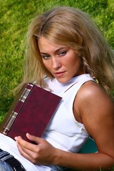 Joven estudiante atractivo leyendo el libro