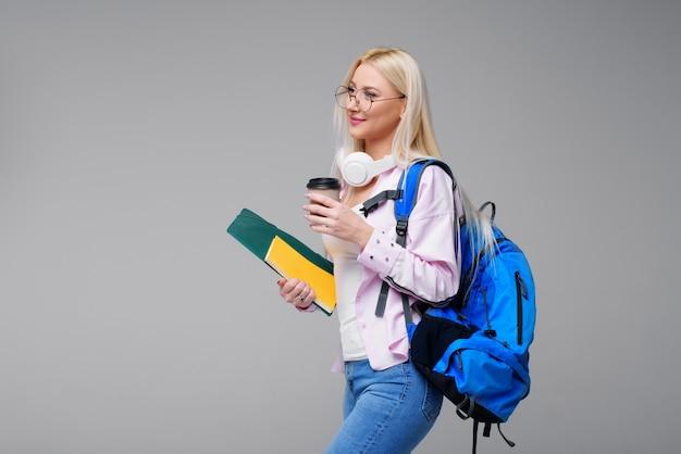 Joven estudiante en auriculares con mochila beber café, sonriendo. startup, freelance. aprender idiomas extranjeros en línea, preparación de exámenes