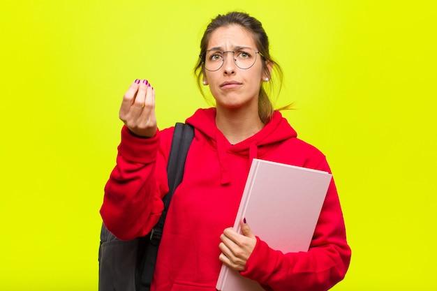 Joven estudiante bonita haciendo capice o gesto de dinero, ¡diciéndote que pagues tus deudas!